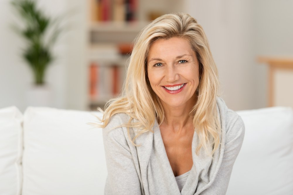 Lovely middle-aged blond woman with a beaming smile sitting on a sofa at home looking at the camera-1